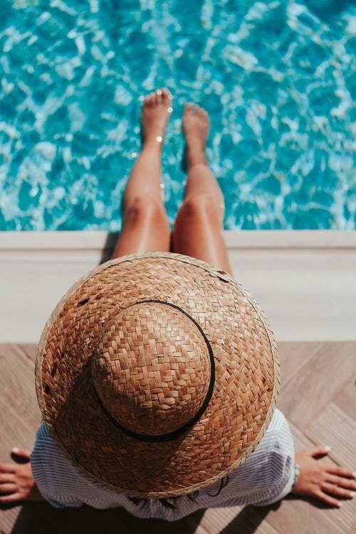 Femme avec chapeau et les pieds dans la piscine
