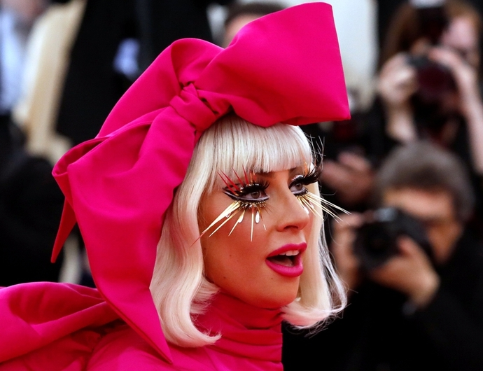 Lady Gaga avec une perruque blonde carré à frange droite et un ruban rose fluo