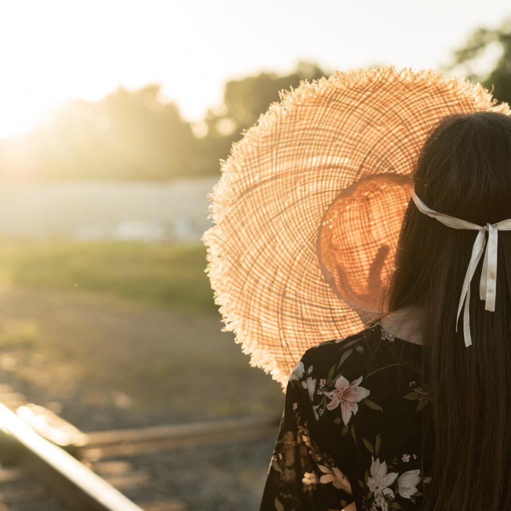 Femme qui cache le soleil avec un chapeau devant sa tête